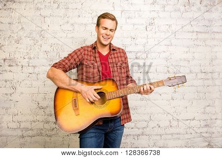 Young Successful Musician Playing On Guitar And Singing