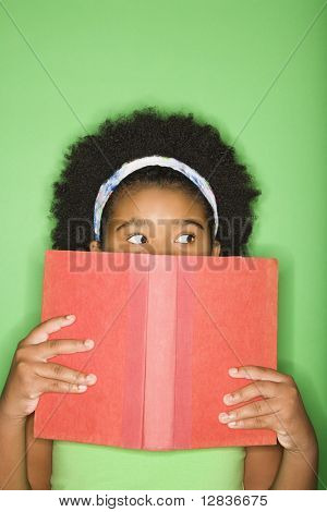 African American girl with book held up to face looking suspiciously to the side.