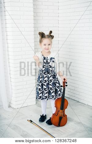 little girl with a violin threatens fist looking at camera