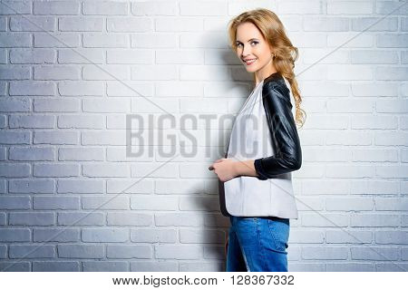 Positive young woman in casual clothes standing by a white brick wall and smiling to camera.