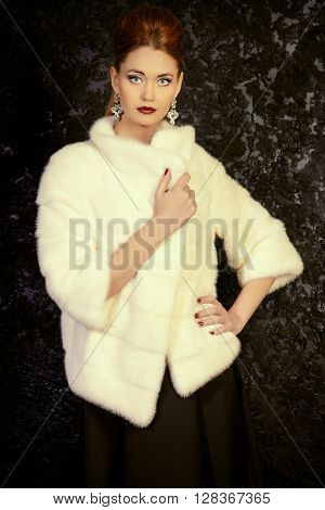 Beautiful young woman wearing mink fur jacket. Jewellery. Beauty, fashion. Studio shot.