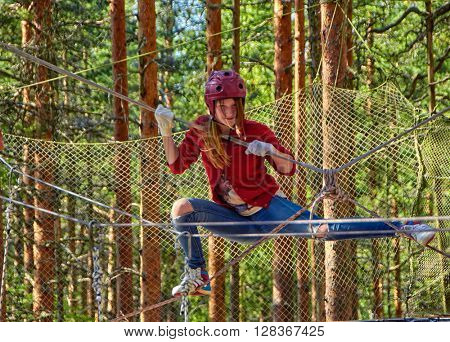 Teen Girl passing through obstacles in a Forest Rope Park Challenge