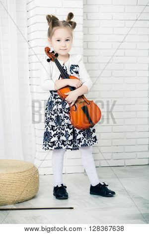 little girl hugging a violin looking at camera