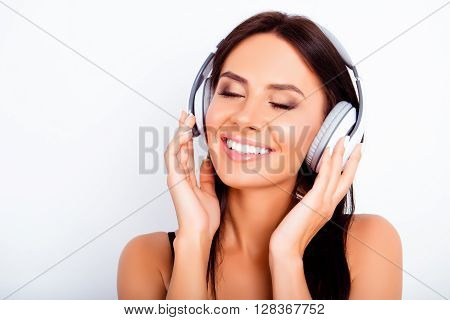 Pretty Young Woman Listening Music In Headphones With Closed Eyes