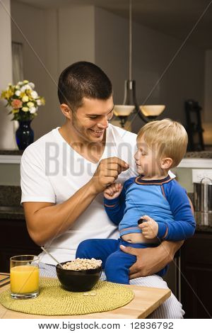 Caucasian man feeding toddler son on lap in kitchen.