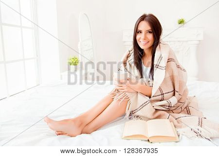 Young Woman Reading Book While Siting On Bed With Cup Of Tea