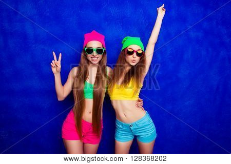 Stylish Young Woman In Glasses Pouting While Her Sister Gesturing With Two Fingers