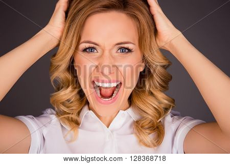 Close Up Portrait Of Angry Sad Woman Yelling And Holding Head
