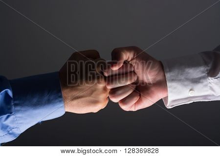Side view with light source from below of fist bump handshake between businessmen over dark gray background