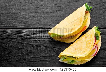 Taco with fresh vegetables and meat on a black wooden surface