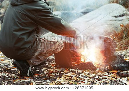 Man making fire in mountains