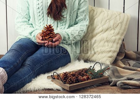 Woman holding pine cone and wooden basket with evergreen