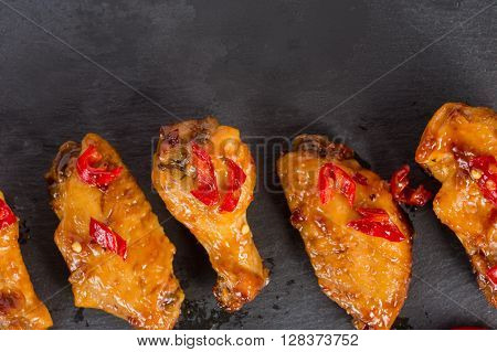 fried chicken wings on a black slate plate with red pepper