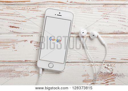 WROCLAW, POLAND - APRIL 12, 2016: Apple iPhone SE smartphone with Google logo on screen