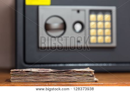 Closeup On Banknotes  In Front Of Safety Box With Electronic Lock In Hotel