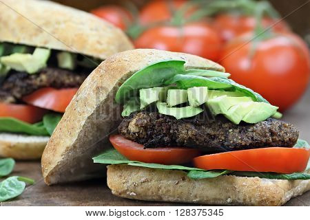 Vegetarian hamburger made from ground mushrooms with avocados tomatoes and spinach. Dairy and meat free. Extreme shallow depth of field with selective focus.