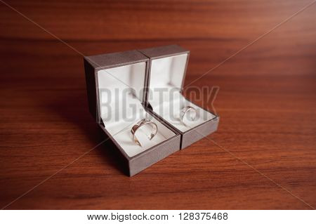 wedding rings white gold in boxes on wooden table