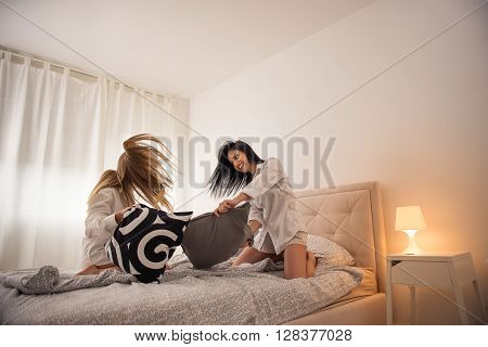 Girls having a pillow fight in a bedroom.