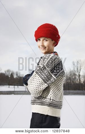 Portrait of Caucasian boy wearing sweater and red winter cap standing looking over shoulder and smiling at viewer.