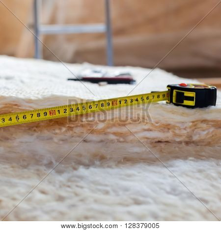 Measure Tape And Knife On Mineral Wool