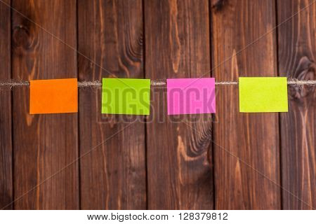 Colorful Stickers Hanging On Clothesline Against Wooden Background