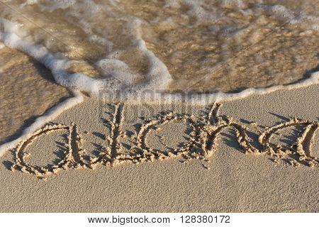 Inscription Aloha On Sandy Beach With Wave's Foam