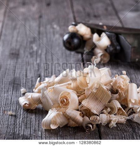 Planer and sawdust on wooden background, closeup