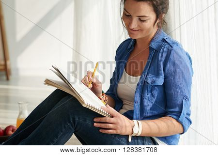 Smiling woman describing her day in diary