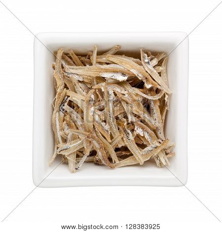 Dried anchovies in a square bowl isolated on white background