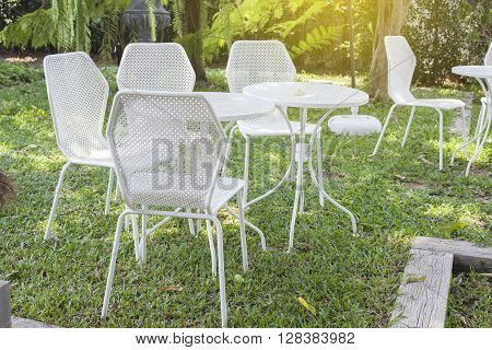 Garden table and white chairs in the green garden