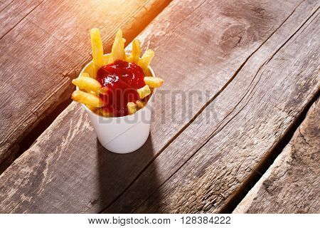 Cup of fries with ketchup. French fries with tomato sauce. Portion of fries on table. Special sauce for snacks.