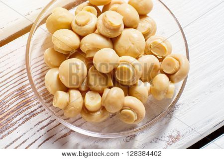 Marinated champignons in glass bowl. Bowl filled with small mushrooms. Cooked champignons on white table. Enjoy the taste.