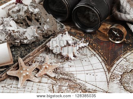 Starfishes shells mineral zeolite specimen compass old binoculars rope and scrolls of paper on a background the ancient map; toned image