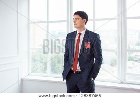 Gorgeous smiling groom. Handsome man in a suite with a buttonhole standing against a window indoors