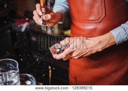 barman breaking ice behind bar no face