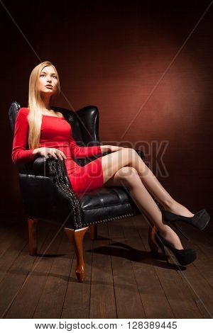 Portrait of a stunning fashionable model sitting in an armchair. Business, elegant businesswoman. Interior, furniture.