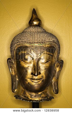 Bronze Buddha head from Thailand against yellow wall.