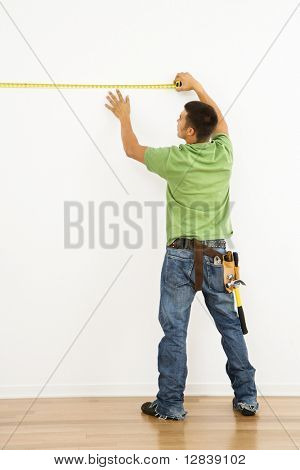 Man wearing tool belt measuring interior wall.