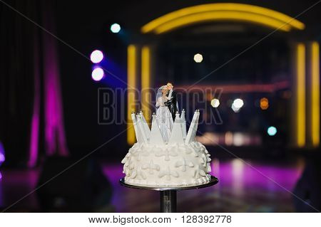 Couple of figurines on top of wedding cake. Spotlights light on the background.