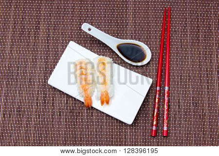 Nigiri with shrimp on a bamboo mat seen from above