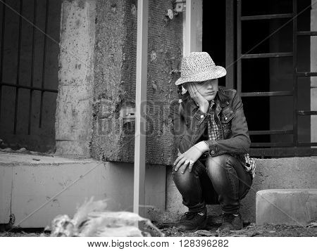 Girl teenager in an abandoned construction site. Ruins. Social, black - white. Concept - stress, teen complexes. Vagrancy, escape from home