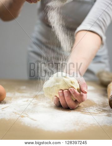 Closeup of female baker's hands kneading dough in bakery.