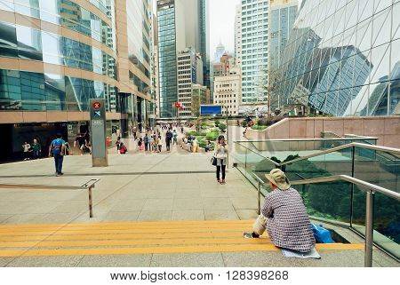 HONG KONG, CHINA - FEB 13, 2016: People making pictures and walking around downtown with skyscrapers and modern architecture structures on February 13, 2016. There are 1223 skyscrapers in Hong Kong.