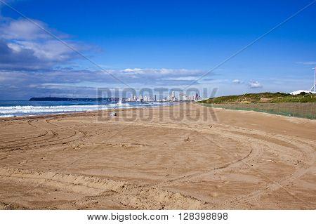 Empty Beach Against City Skyline And Blue Cloudy Sky
