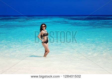 Beautiful Sexy Bikini Model. Tropical Beach. Outdoor Portrait Of Slim Brunette Woman Sun Tanning Pos