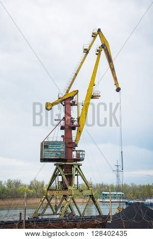port crane behind the barbed wire on the bank