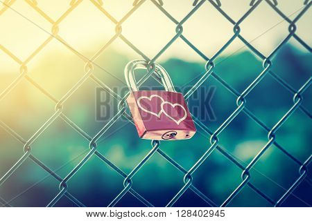 Lock symbolizing love forever on the fence with soft light and vintage style