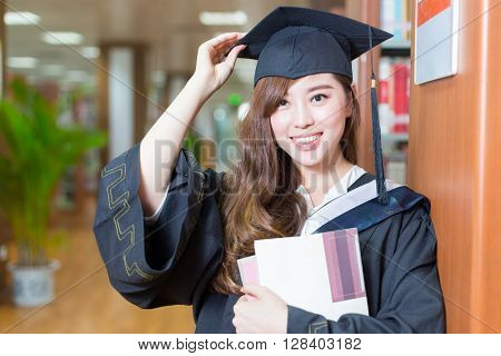young beautiful asian girl university student with Bachelor gown in library