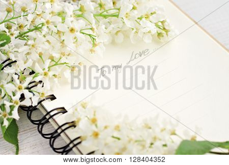 Romantic love note. Note book and spring tree blossom. Text in pencil handwritten