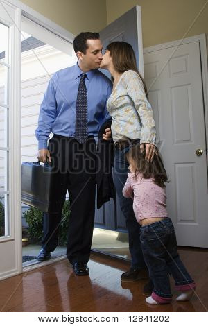 Caucasian businessman   at open door kissing wife while daughter hugs her leg.